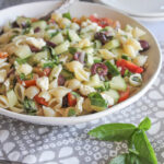 A close up picture of greek pasta salad in a white bowl