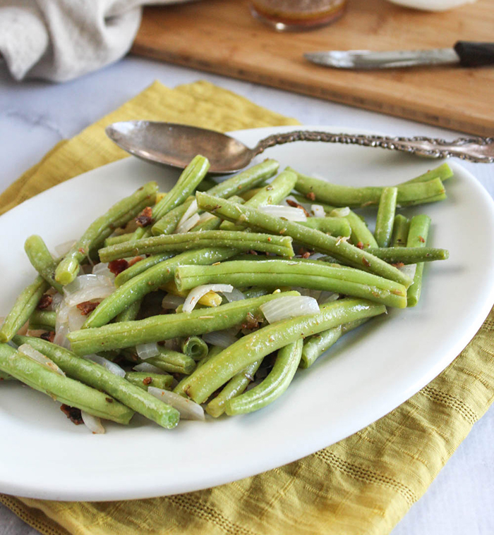 Green beans with bacon on a white plate