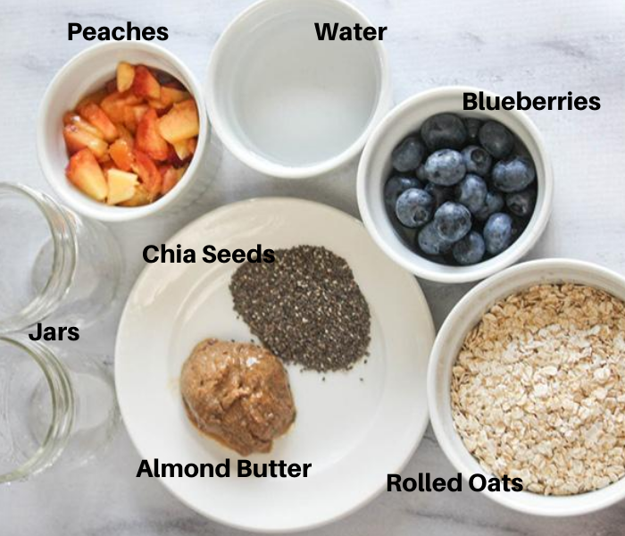 An overhead view of the ingredients in white bowls:  chopped peaches, water, blueberries, oatmeal, chia seeds, almond butter and 2 jars