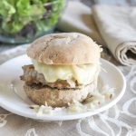 turkey burger on a roll with sauerkraut and melting cheese on a white plate