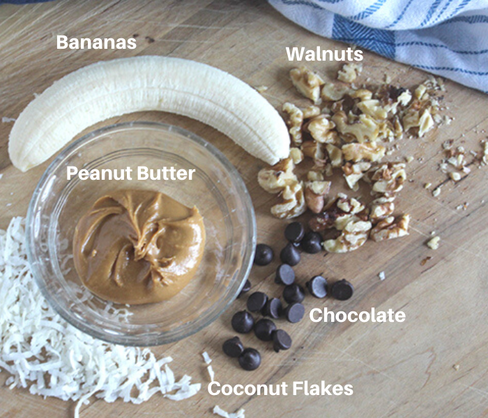 The ingredients for banana sushi on a cutting board: coconut shreds, chocolate chips, walnuts, peanut butter and a banana