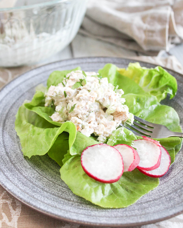 A close up of chicken salad on lettuce with raddish slices on a plate with a fork