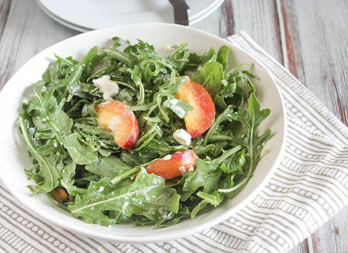 an overhead view of peach arugula salad with goat cheese in a white bowl