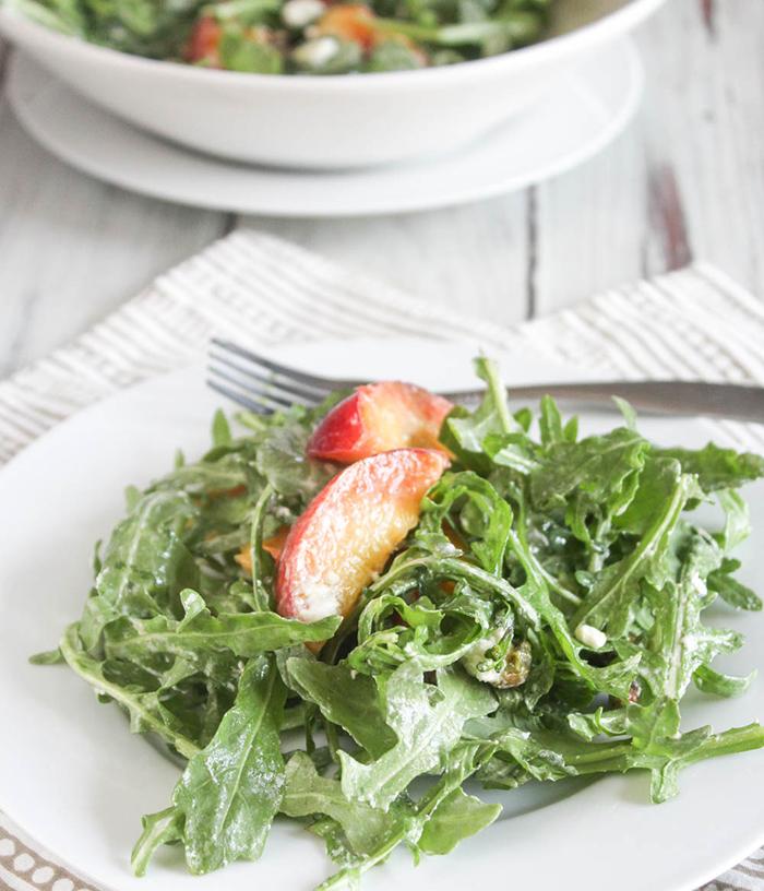 a close up of peach arugula salad on a plate