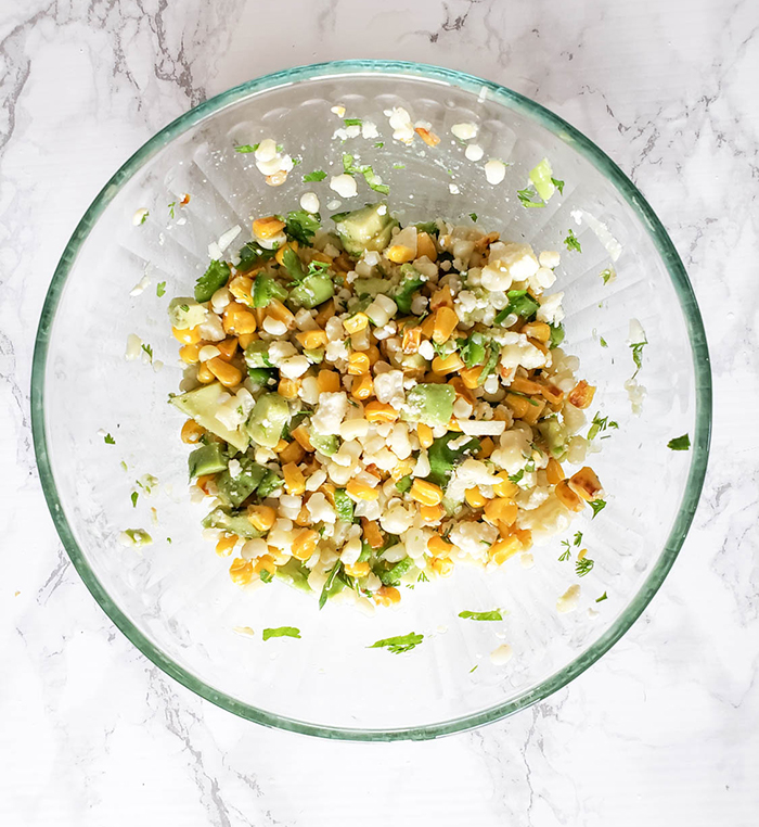 an overhead view of the corn salad mixed in a glass bowl