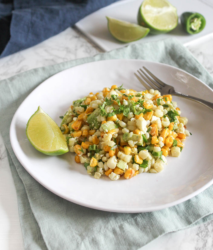 A plate full of mexican corn salad with a fork and slice of lime