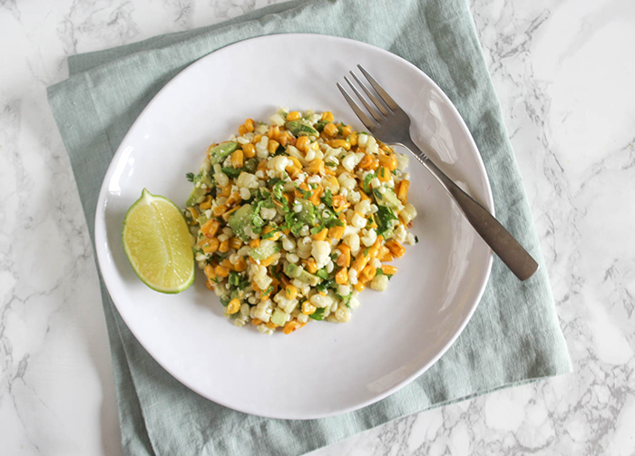 an overhead shot of corn salad on a white plate with a fork