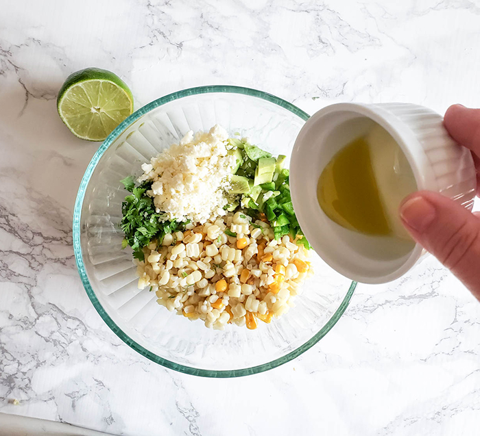 corn slaad ingredients in a bowl with lime juice being poured in