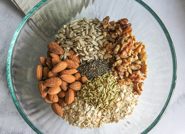 dry ingredients in a mixing bowl: almonds, walnuts, chia seeds, fennel seeds, sunflower seeds