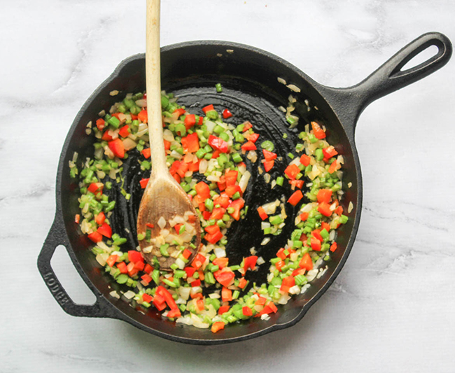diced celery, bell peppers and onions cooked in a skillet with a wooden spoon