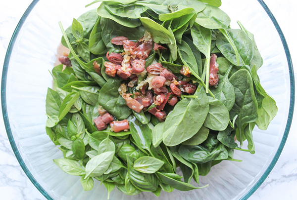 spinach, basil in a bowl with the oil garlic and prosciutto on top