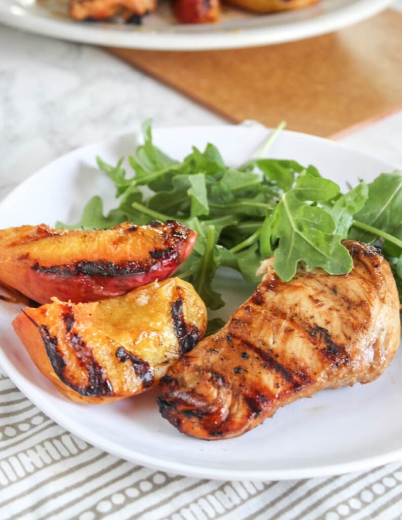 Grilled peaches and chicken on a plate with arugula
