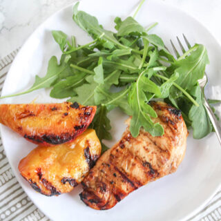 an overhead viewof grilled peaches and chicken on a white plate
