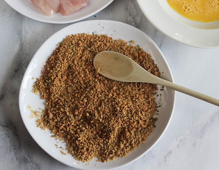bread crumbs mixed with spices on a plate with a wooden spoon