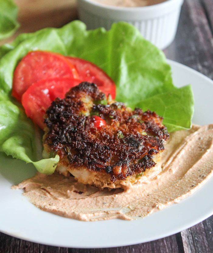 A close up picture of a shrimp cake cooked on a plate with lettuce and tomatoes
