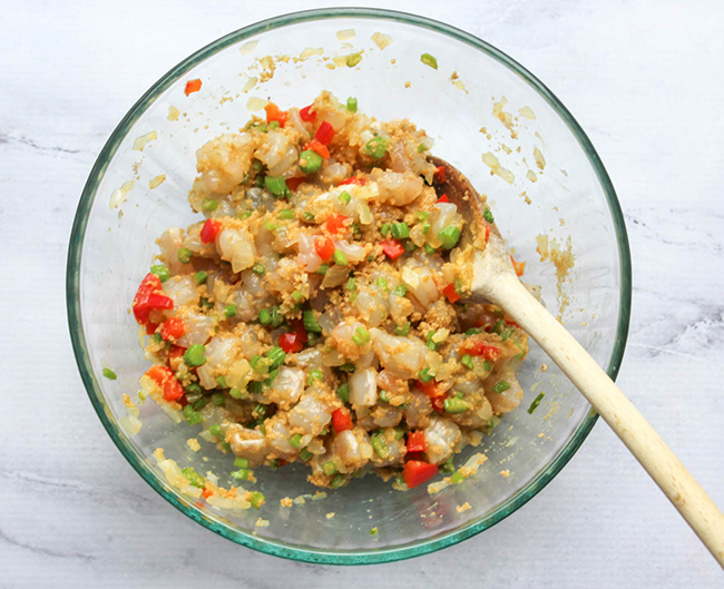 shrimp mixture for the cakes in a bowl with a spoon