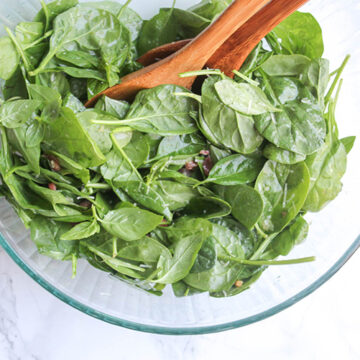 overhead view of mixed spinach salad in a galss bowl