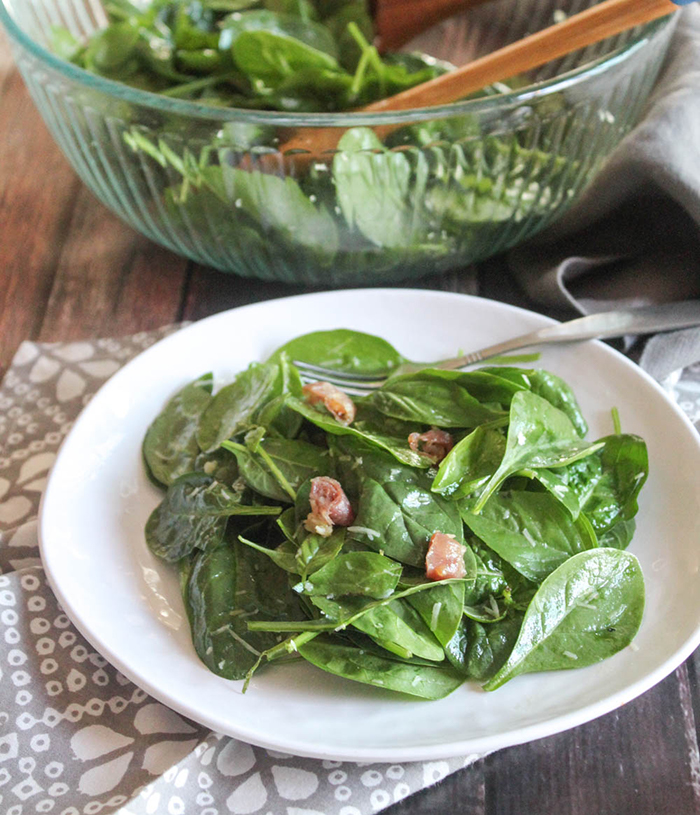 a close up picture of spinach salad on a plate with a glass salad bowl in the background with salad in it