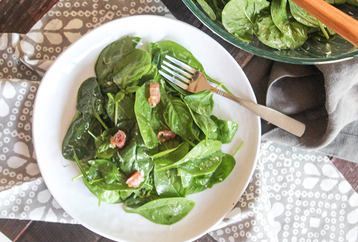 an overhead view of the spinach salad on a white place