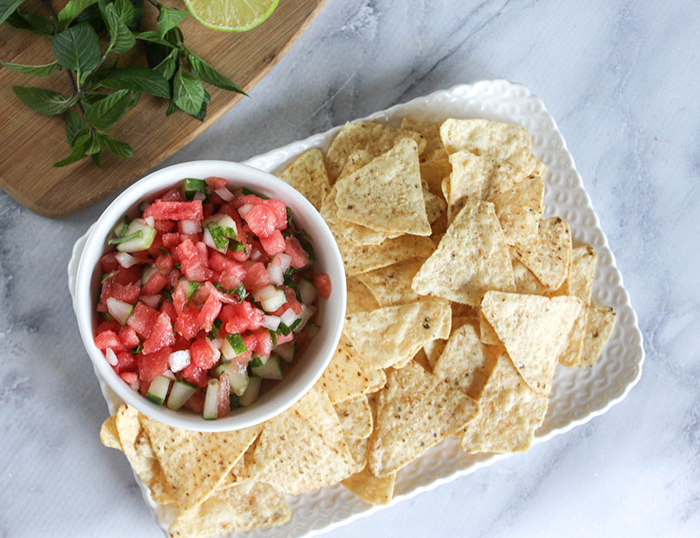 a view looking down at the watermelon salsa in a white bowl with a tray of chips