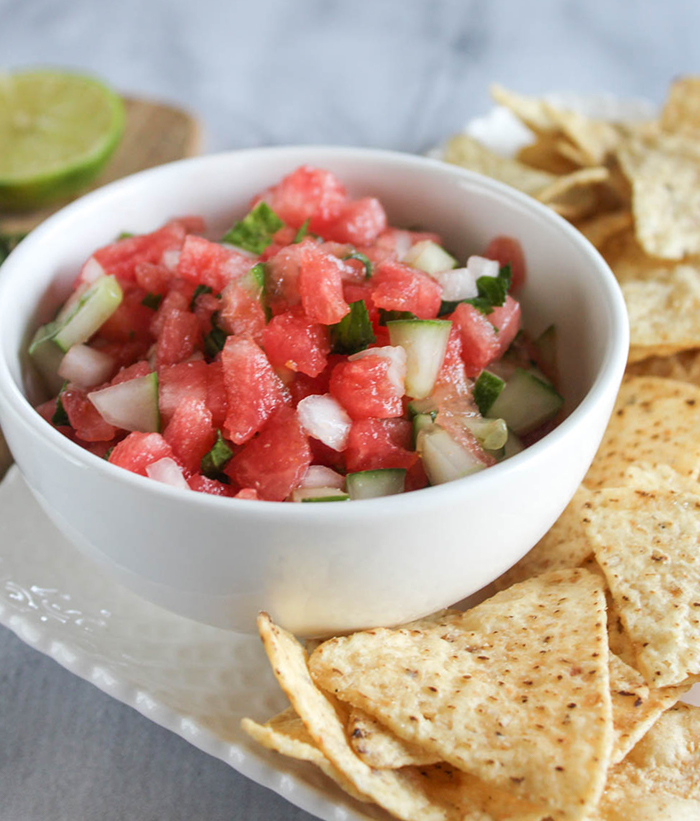 watermelon and cucumber salsa in a white bowl surrounded by chips