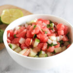 a close up of the finihsed salsa in a white bowl