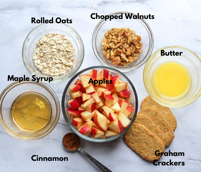 The ingredients for apple crisp in bowls: rolled oats, chopped walnuts, melted butter, maple syrup, apples, cinnamon, graham crackers