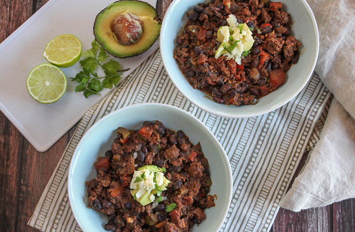 an overhead view of bison chili in two blue bowls with avocado and limes on the side
