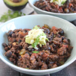 close up photo of bison chili topped with chopped avocado and cheese