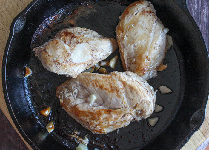 chicken cooking  in a pan with garlic