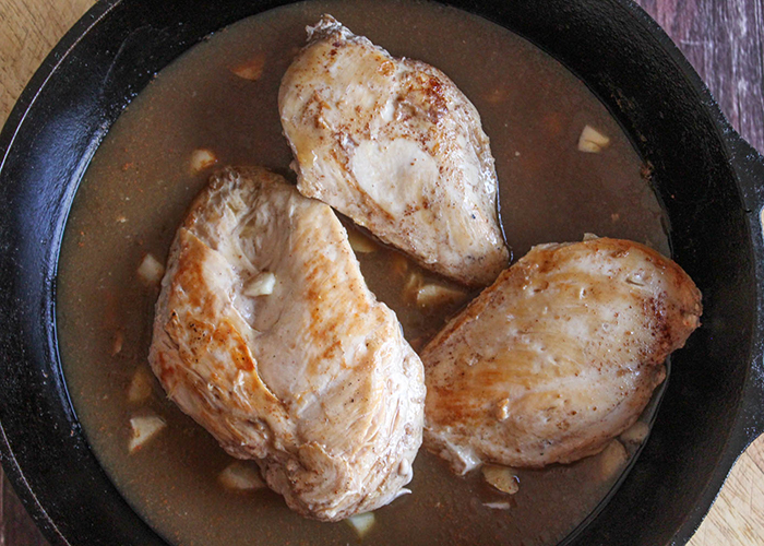 CHicken in a skillet with a brown sauce