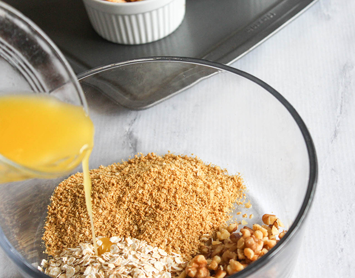 butter pouring into a bowl of oats and crumbs
