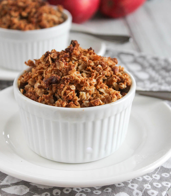 mini apple crisp in a white ramekin dish on a white plate