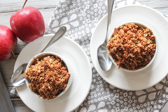 an overhead view of two portions of apple crisp in two separate white ramekins on a white plate