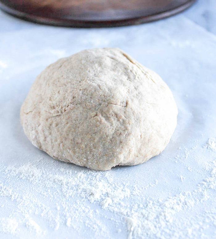 a dough ball on a piece of white parchment with flour