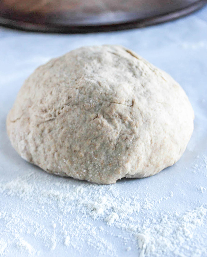 a close up of the dough ball on white parchment with flour