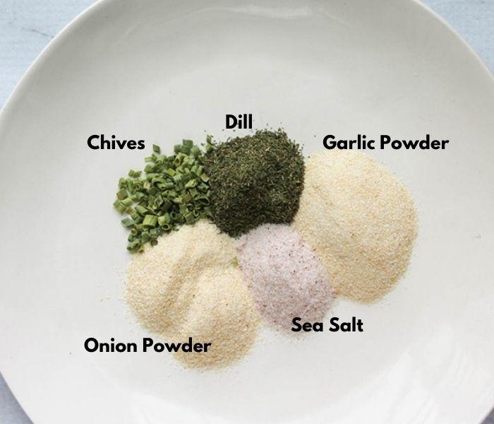 The ingredients on a plate: dried chives, Dill, garlic powder, onion powder, sea salt