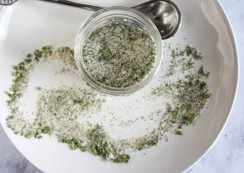 An overhead view of the spice blend in a jar with a spoon on the side
