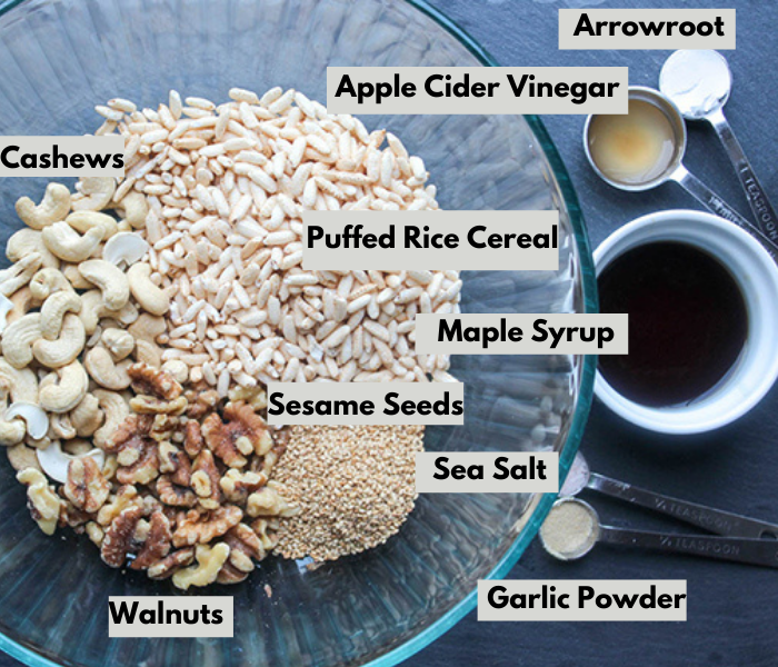 the ingredients in a bowl from left to right: cashews, arrowroot, apple cider vinegar, puffed rice cereal, maple syrup, sesame seeds, sea salt, garlic powder and walnuts