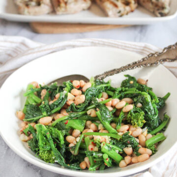 a close up picture of sauteed broccoli rabe in a white bowl with a serving spoon