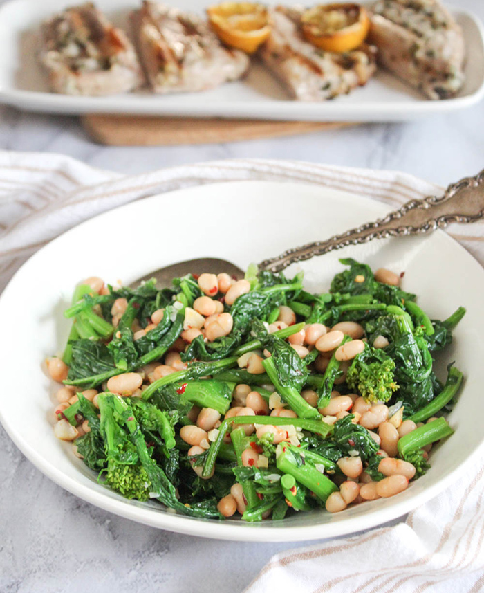 sauteed broccoli rabe with white beans in a white bowl with a serving spoon