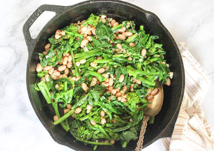 an overhead view of sauteed broccoli rabe in a skillet mixed together with white beans with a serving spoon