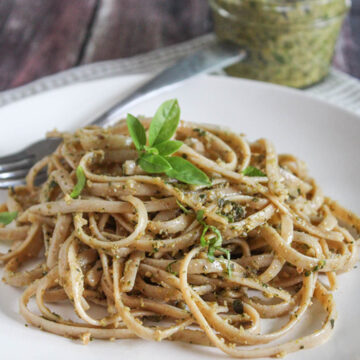 pasta on a plate with a jar of pesto in the background
