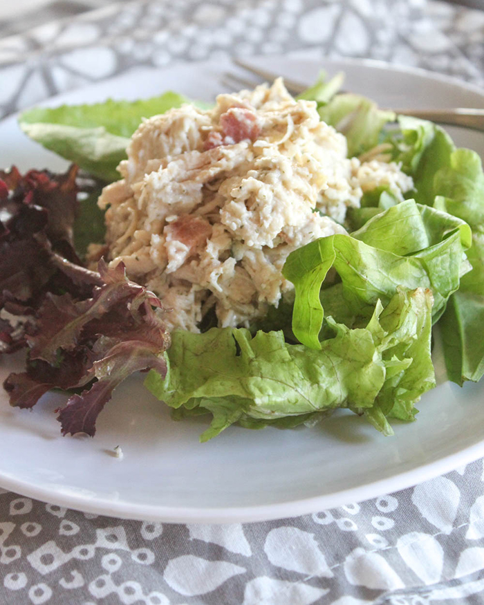 shredded chicken on top of a bed of lettuce,