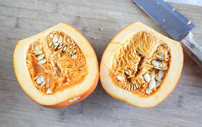 a pumpkin cut in half with a knife on the side
