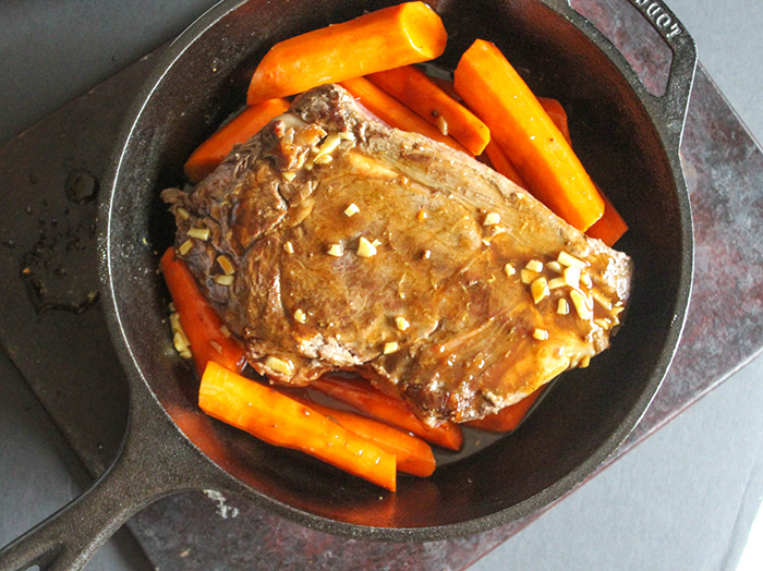 The roast covered with the sauce in a pan with carrots around it