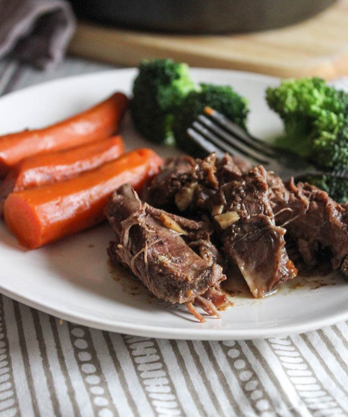 braised chuck roast on a plate with carrots and broccoli