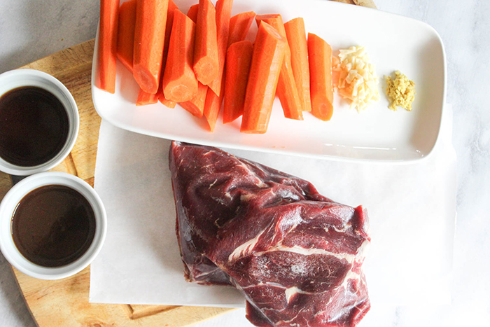 AN overhead view of the uncooked ingredients: beef chuck roast, Kevin's teriyaki sauce, carrots, garlic and ginger