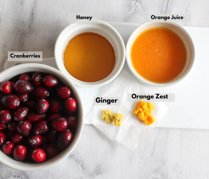 cranberry sauce ingredients left to right Cranberries, honey, orange juice, grated orange zest, grated ginger.