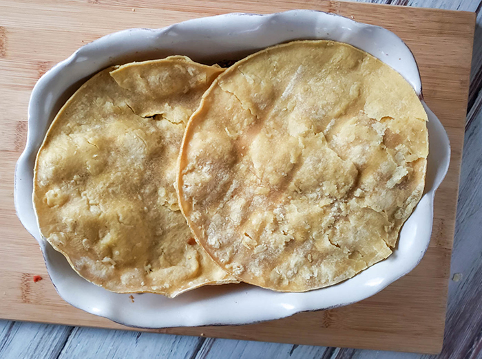 overhead shot of two tortillas on top of the casserole dish